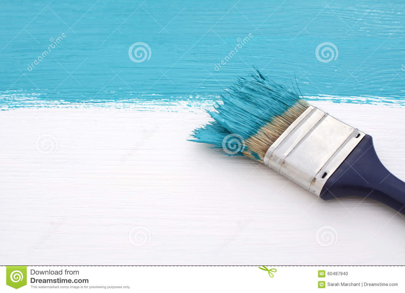 pincel pintando. pincel com a pintura azul, pintando sobre placa branca