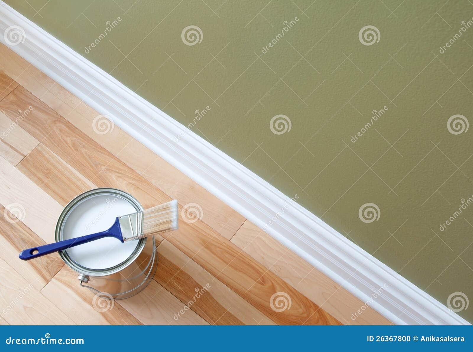 Pincel e uma lata da pintura no assoalho de madeira