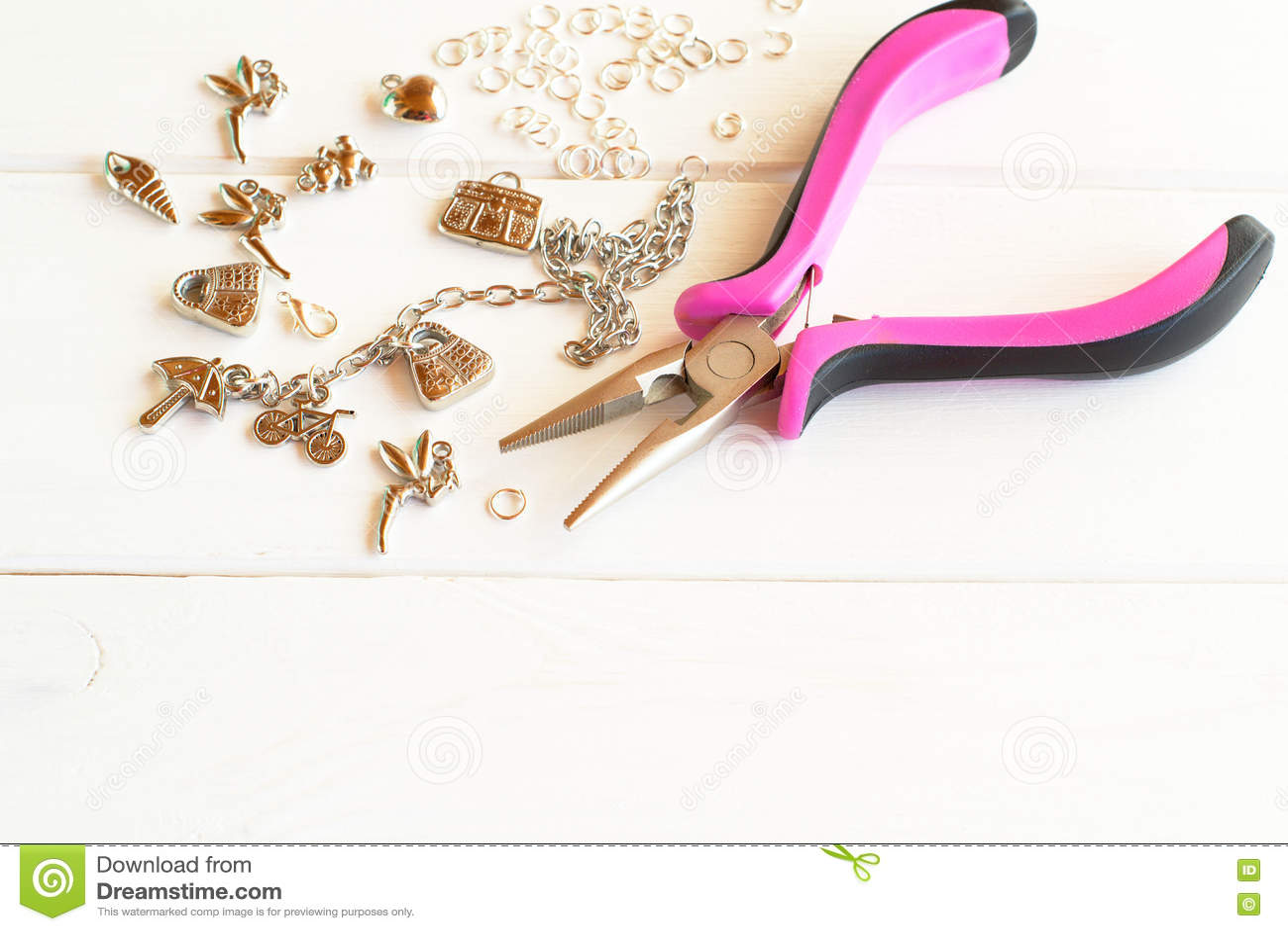 pinces, chaîne, anneaux en métal et pendants sur un fond en bois