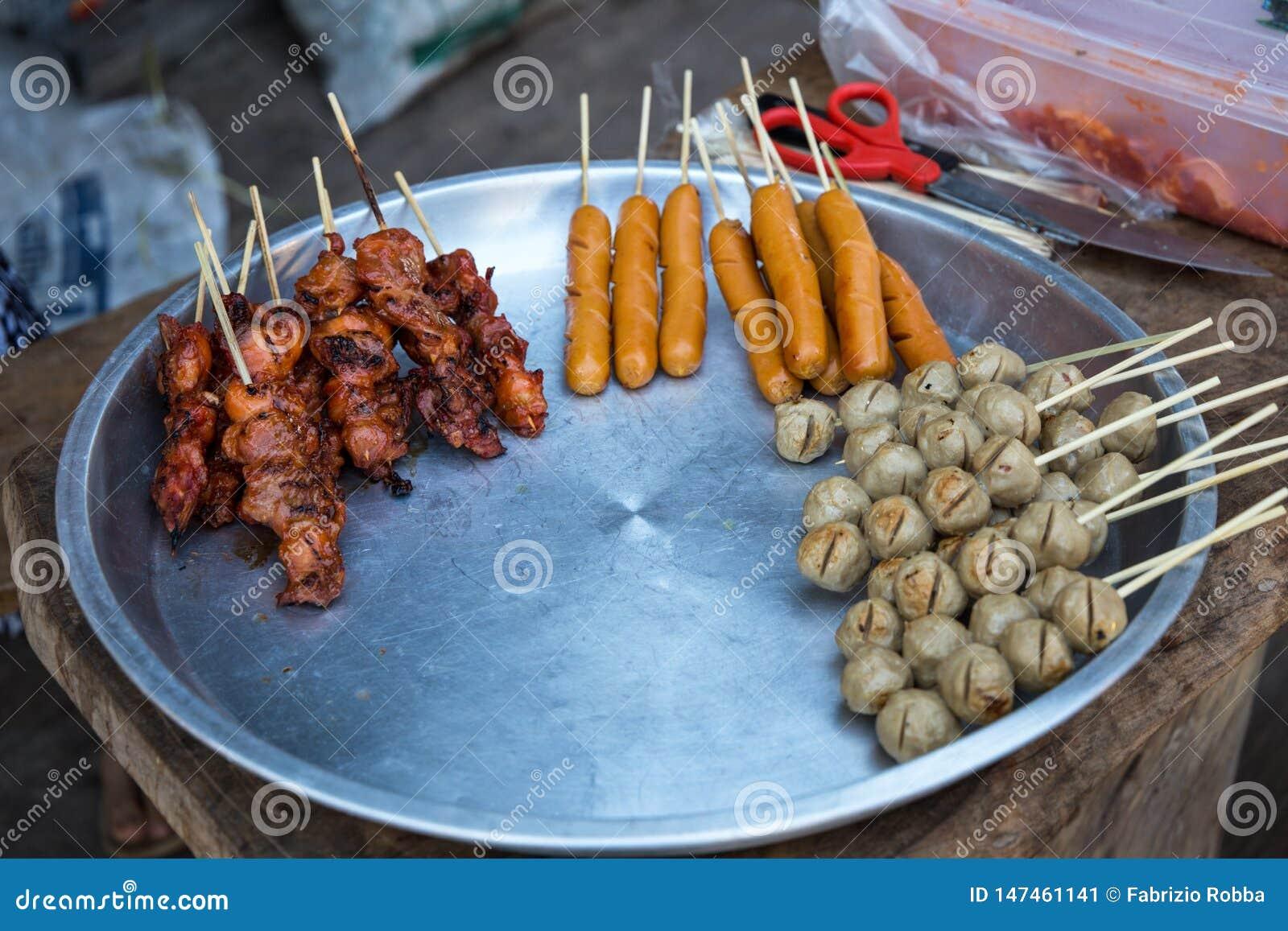 Pinchos asados a la parrilla del cerdo y del pollo en venta en Tailandia