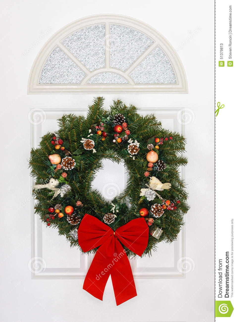 Pine Christmas Wreath With Red Bow Hanging On White Door Stock Image