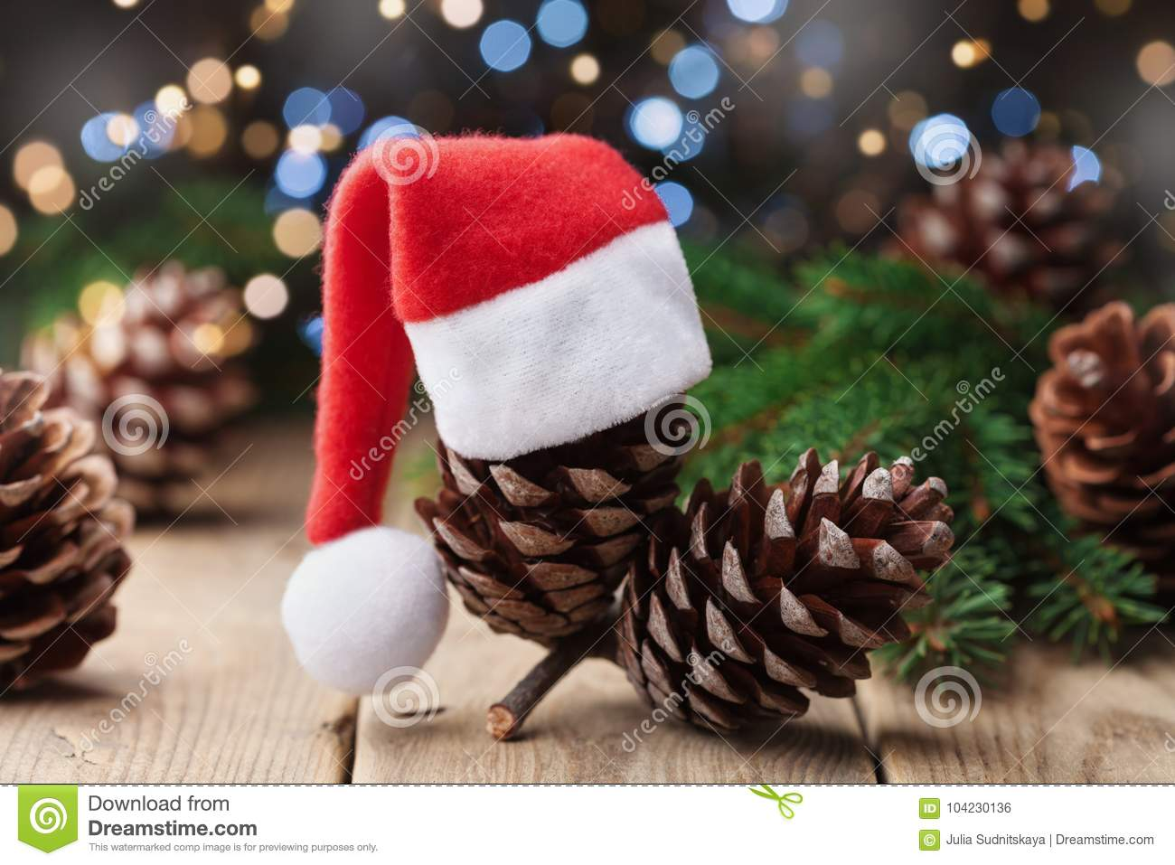 Pine cone decorated Santa hat and fir tree branch on rustic background. Christmas greeting card.
