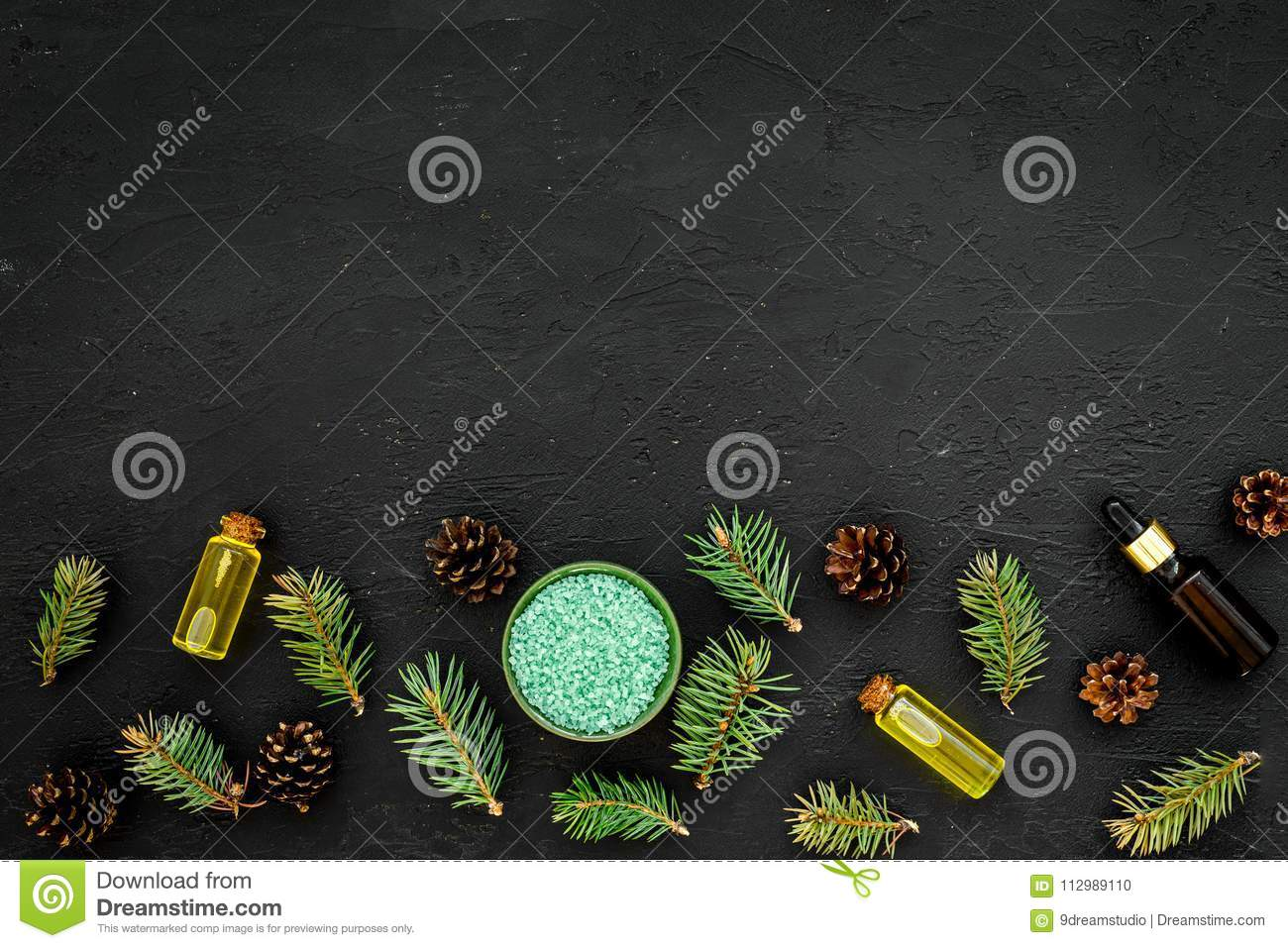 Pine essential oil in bottles on dark background top view copy space. Pattern with pine branch and cone