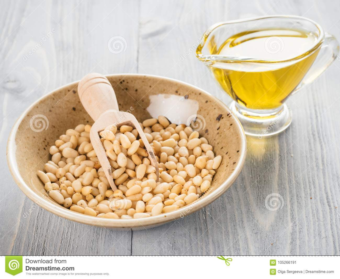 Pine nut oil and pine nuts on gray wooden background