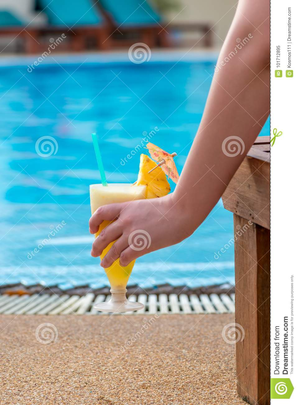 Pineapple cocktail in a woman`s hand, which is sitting in a loun