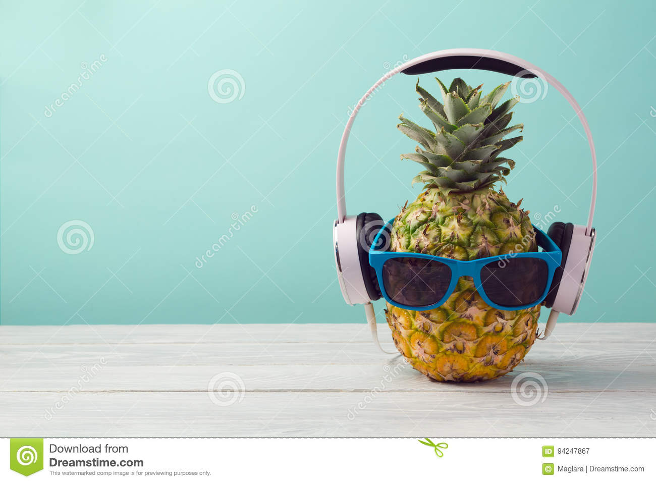 Pineapple with headphones and sunglasses on wooden table over mint background. Tropical summer vacation and beach party.