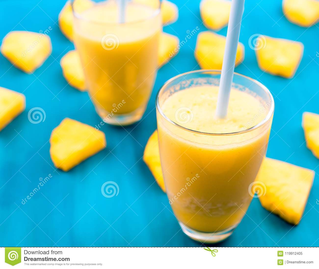 Pineapple smoothie with fresh pineapple on wooden blue table.