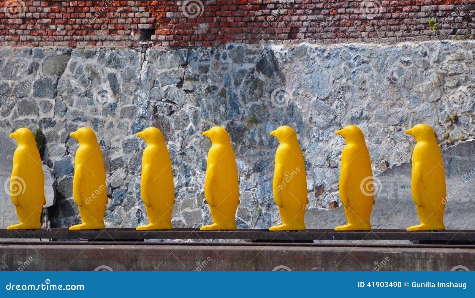 Pingüinos plásticos amarillos en fila
