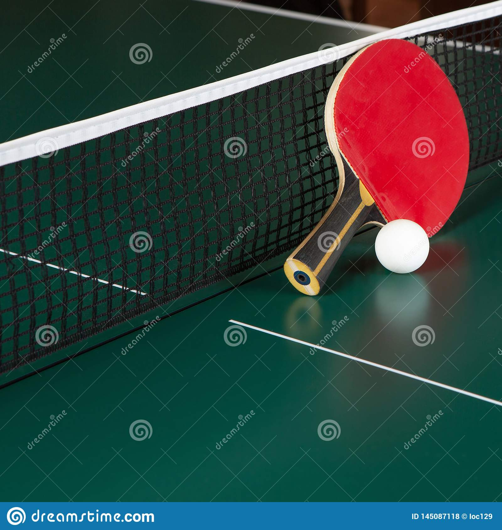 Ping-pong racket and a ball on a green table. Close-up