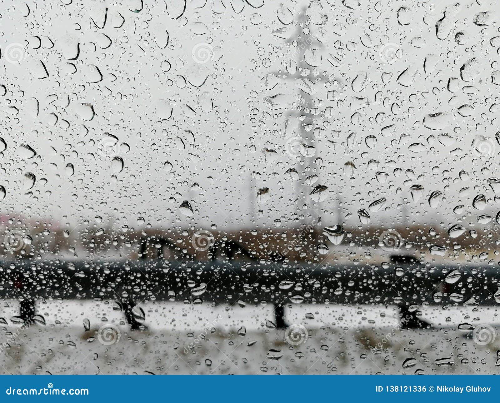 Pingos de chuva na janela de carro na cidade