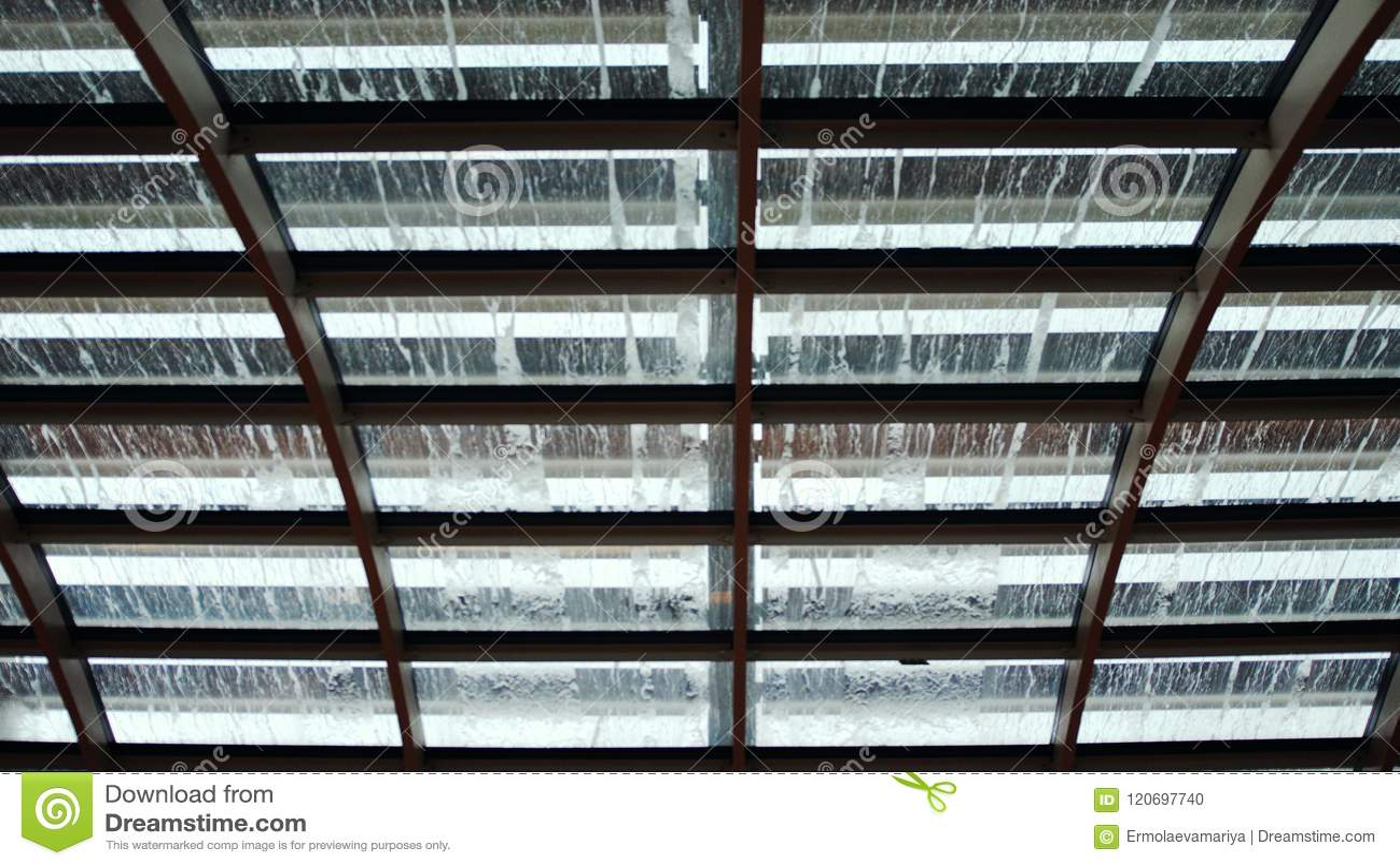 Pingos de chuva no telhado de vidro A vista da parte inferior em gotas da chuva espirra e fluxo para baixo sobre o vidro blurry