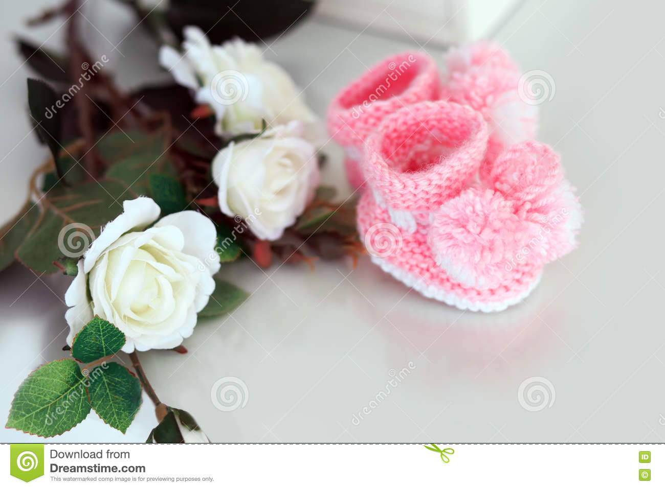 White Roses. Knitted Baby Shoes. Stock