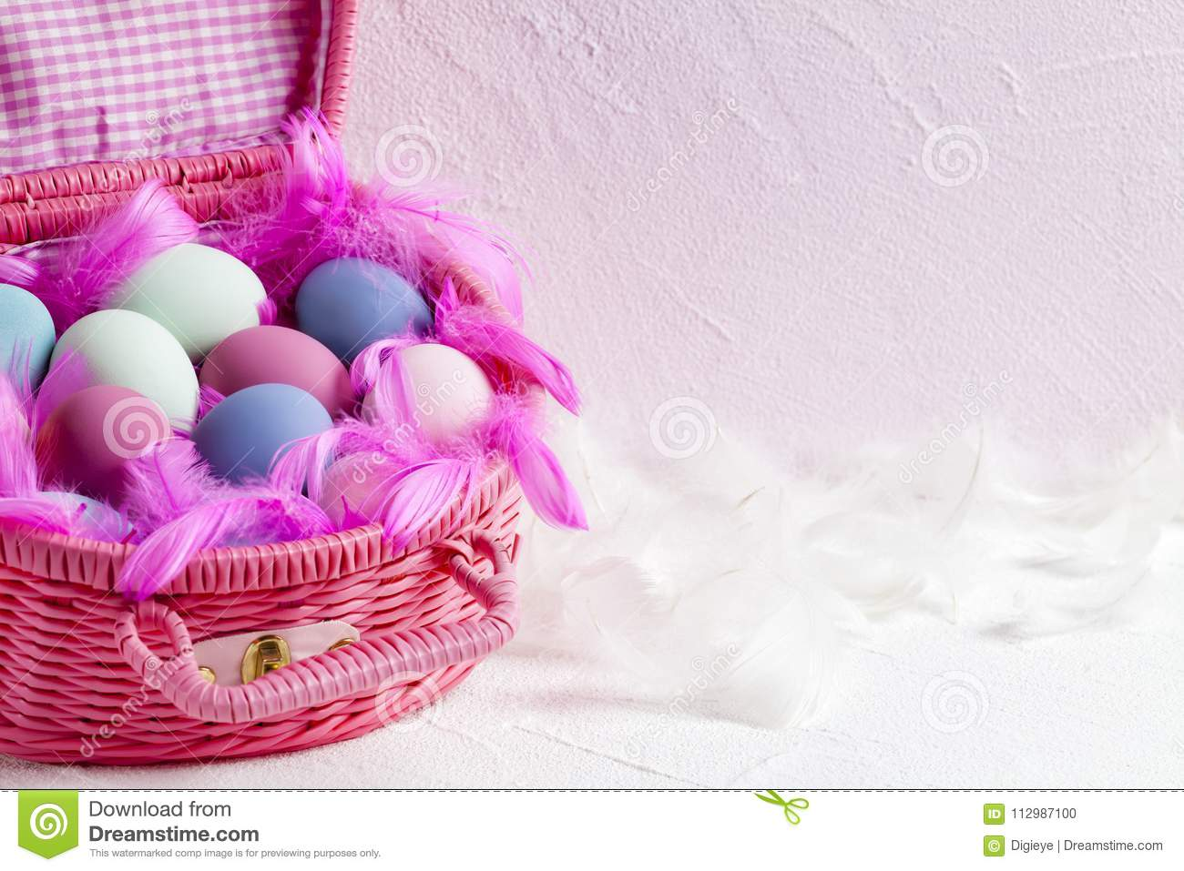 Pink basket full of colored Easter eggs and feathers