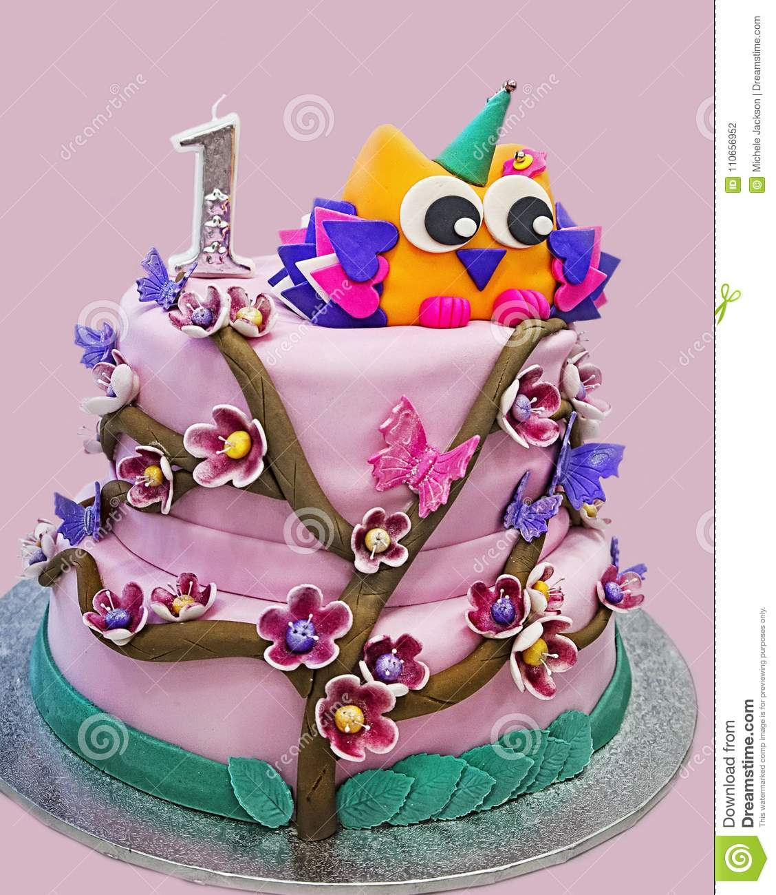 An Elaborate Pink Birthday Cake For A One Year Old Girl Featuring Flowers Butterflies And Owl On Top Wearing Party Hat