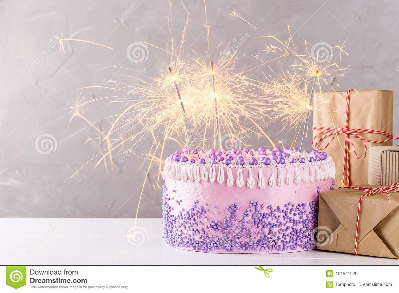 Pink Birthday Cake With Purple Sprinkles And Sparklers Over Gray Background Gift Boxes