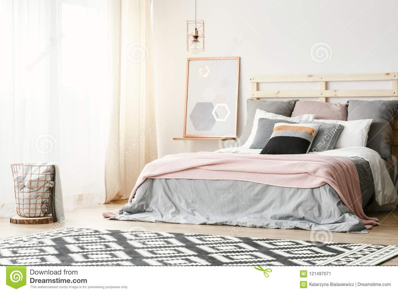 Pink blanket on grey bed in modern bedroom interior with poster