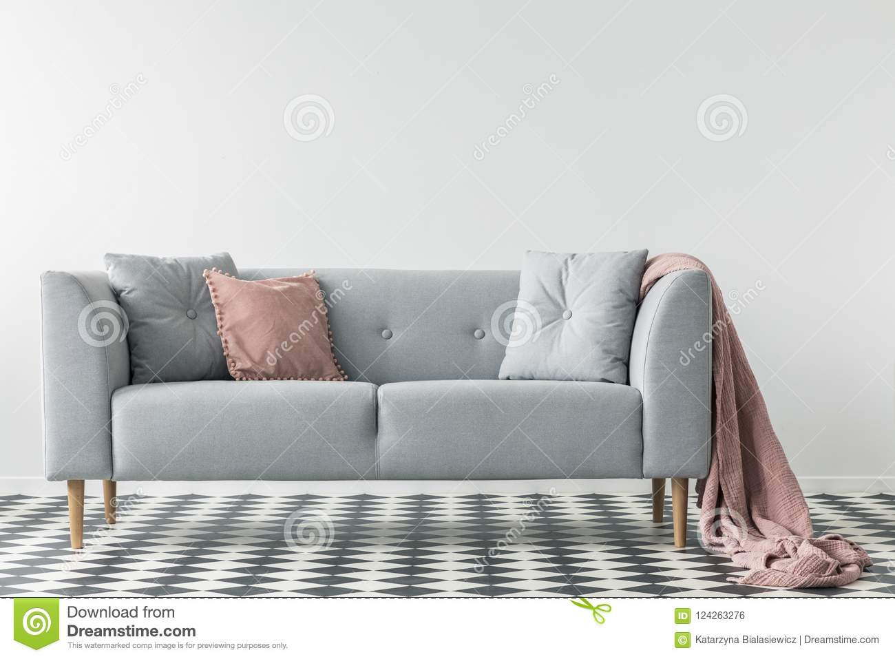 Pink blanket on grey couch with pillows on checkered floor in white living  room interior. b1987d2a3
