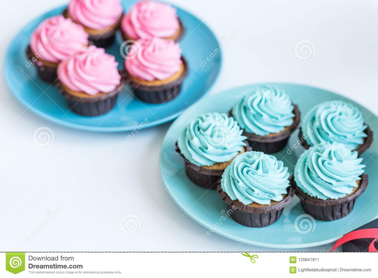 Pink And Blue Cupcakes On Plates On White Table Baby Shower Stock