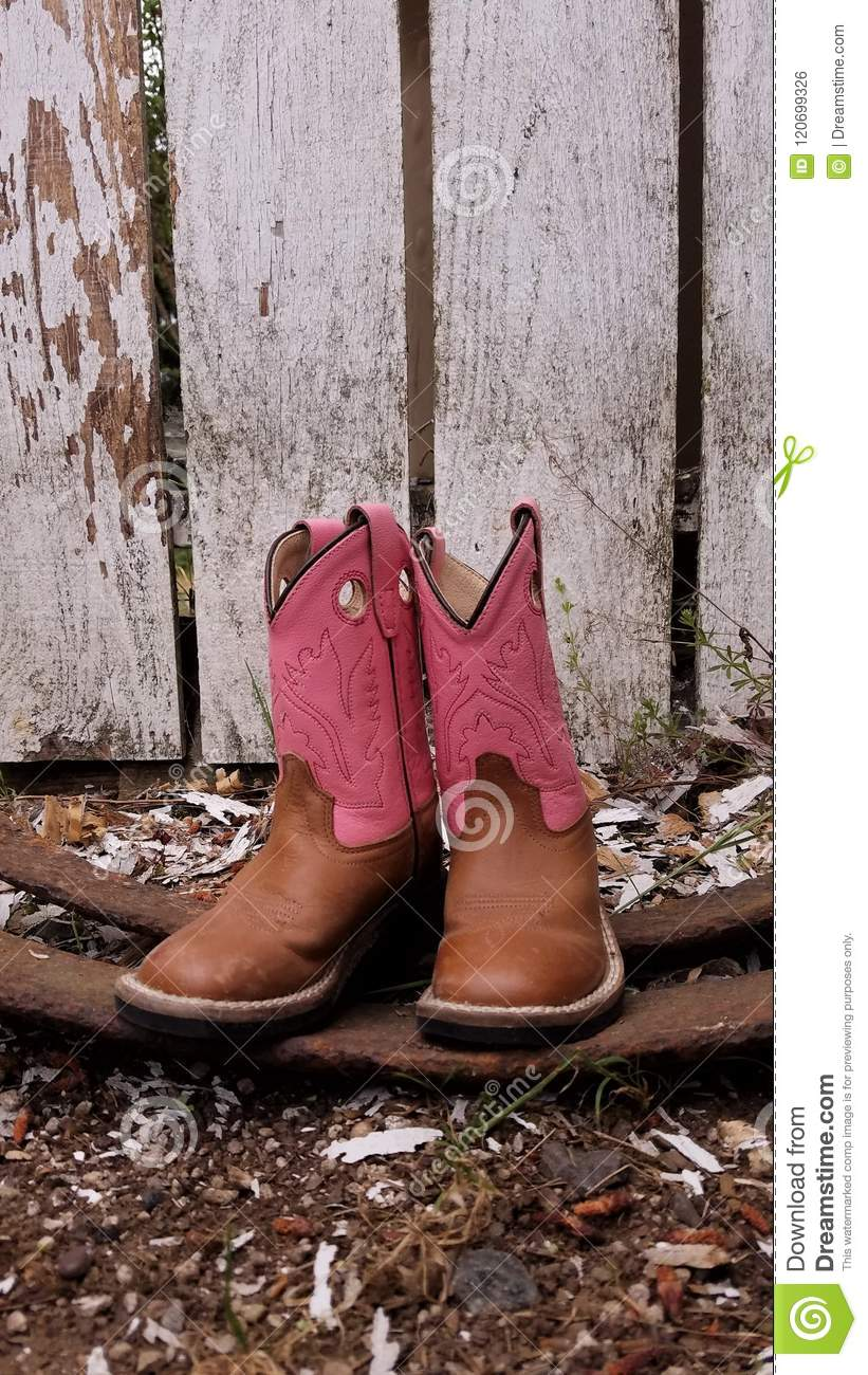 Pink and brown cowboy boots against a rough fence.