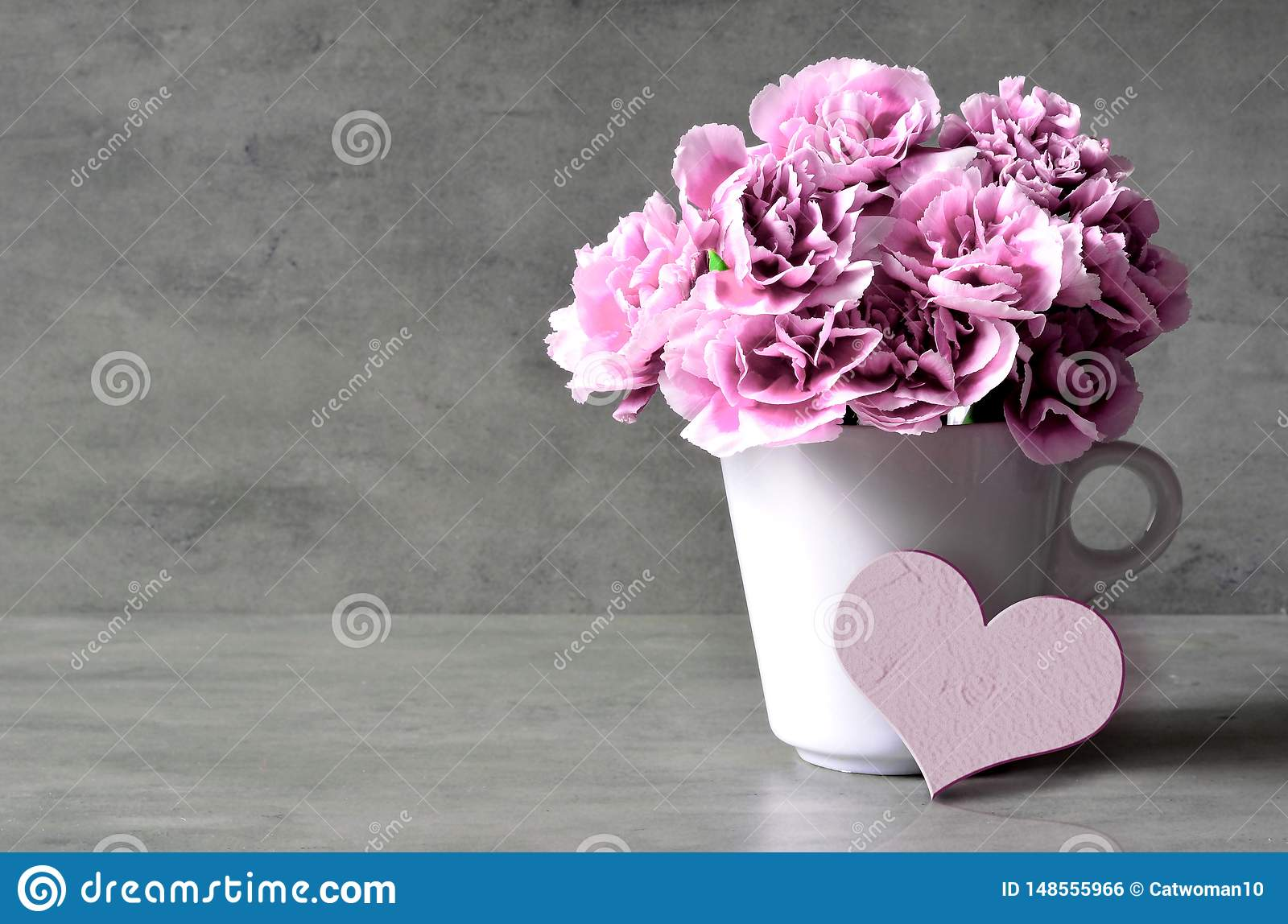 Pink carnation flowers in cup and heart on grey background