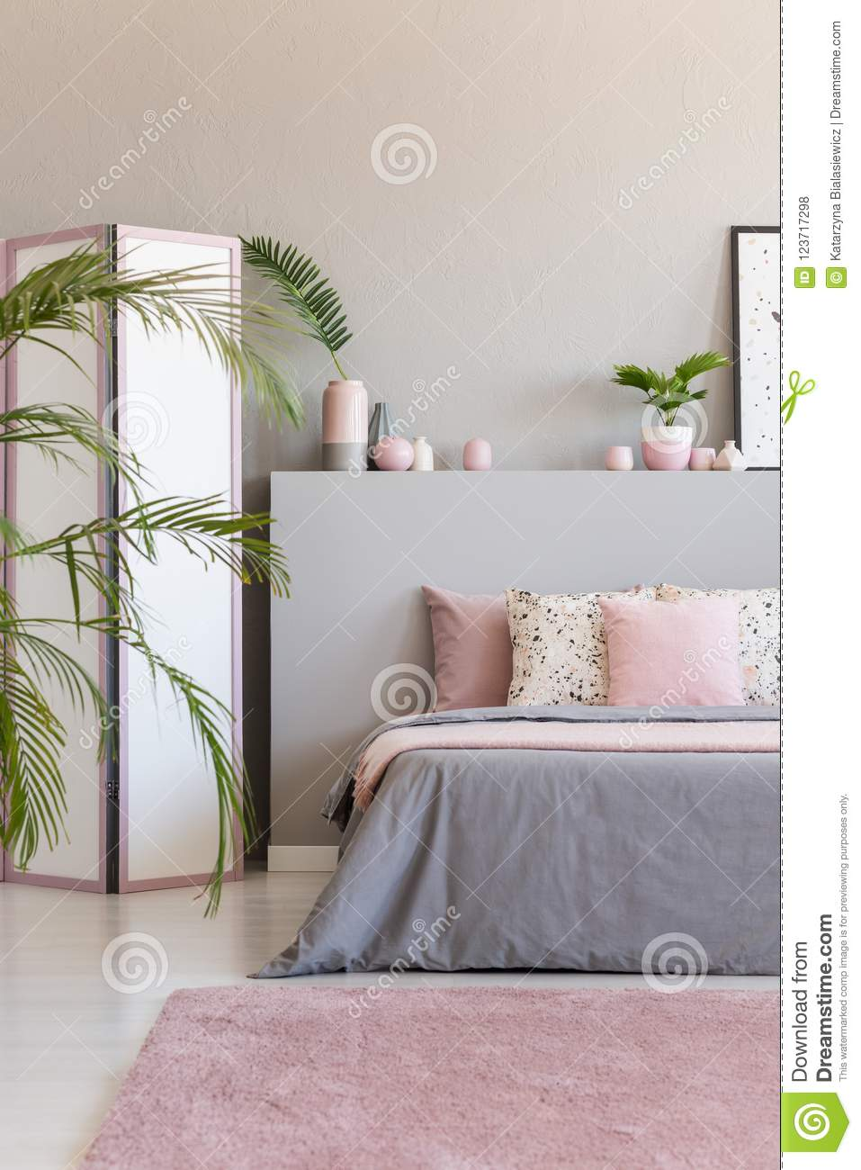 Pink Carpet In Front Of Grey Bed With Cushions In Bedroom Interior ...
