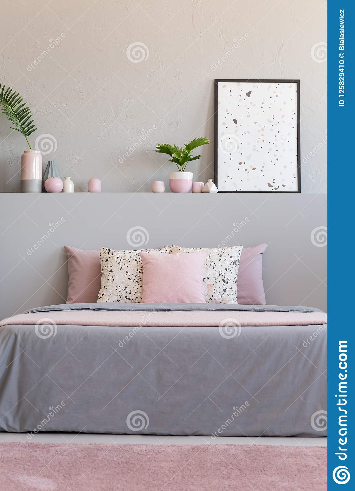 Pink Carpet In Front Of Grey Bed With Cushions In Bedroom ...