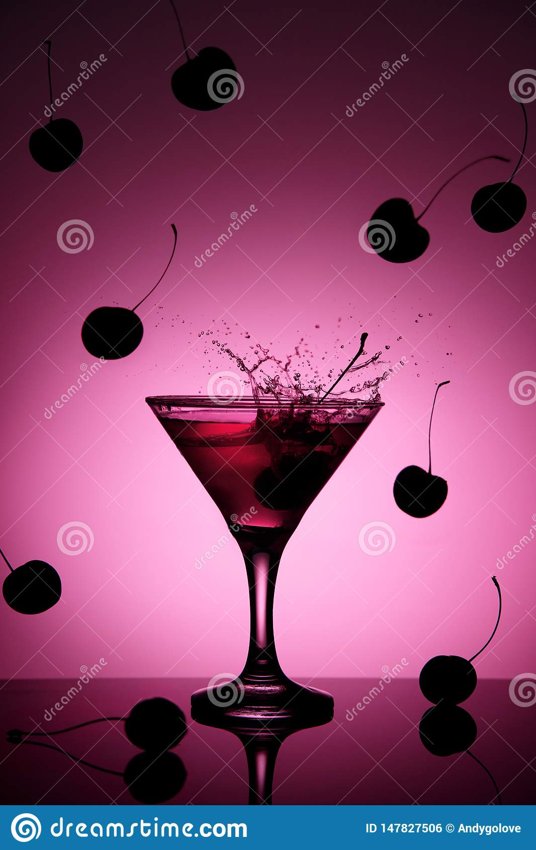 Pink cherry coctail in martini glass with a splash and falling cherries on the background