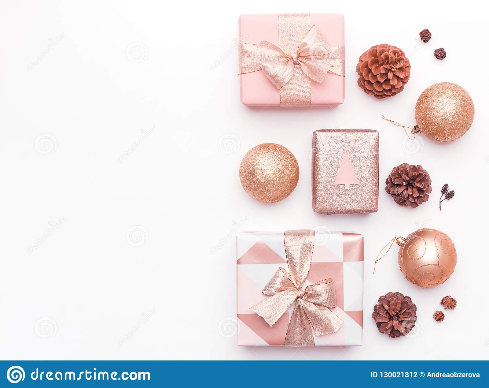 Pink christmas gifts isolated on white background. Wrapped xmas boxes, christmas ornaments, baubles and pine cones.