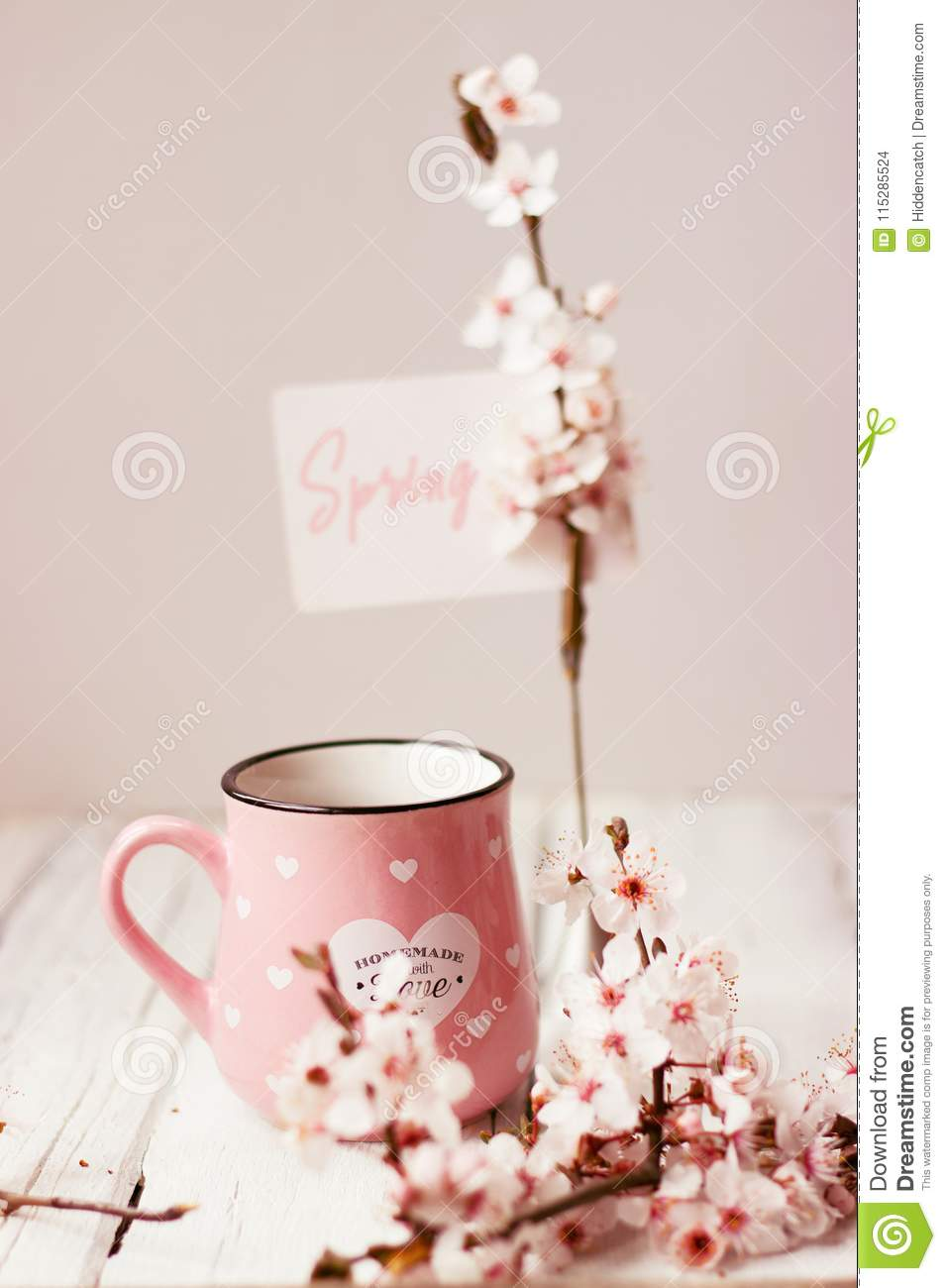 Pink coffee mug, white cherry flowers and `Spring` note; spring background