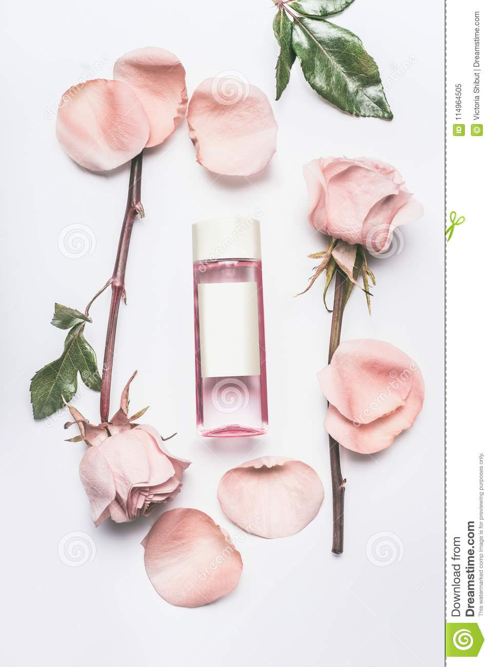 Pink cosmetic bottle with facial roses water or toner with essential oil , flowers and petals on white desk background, top view