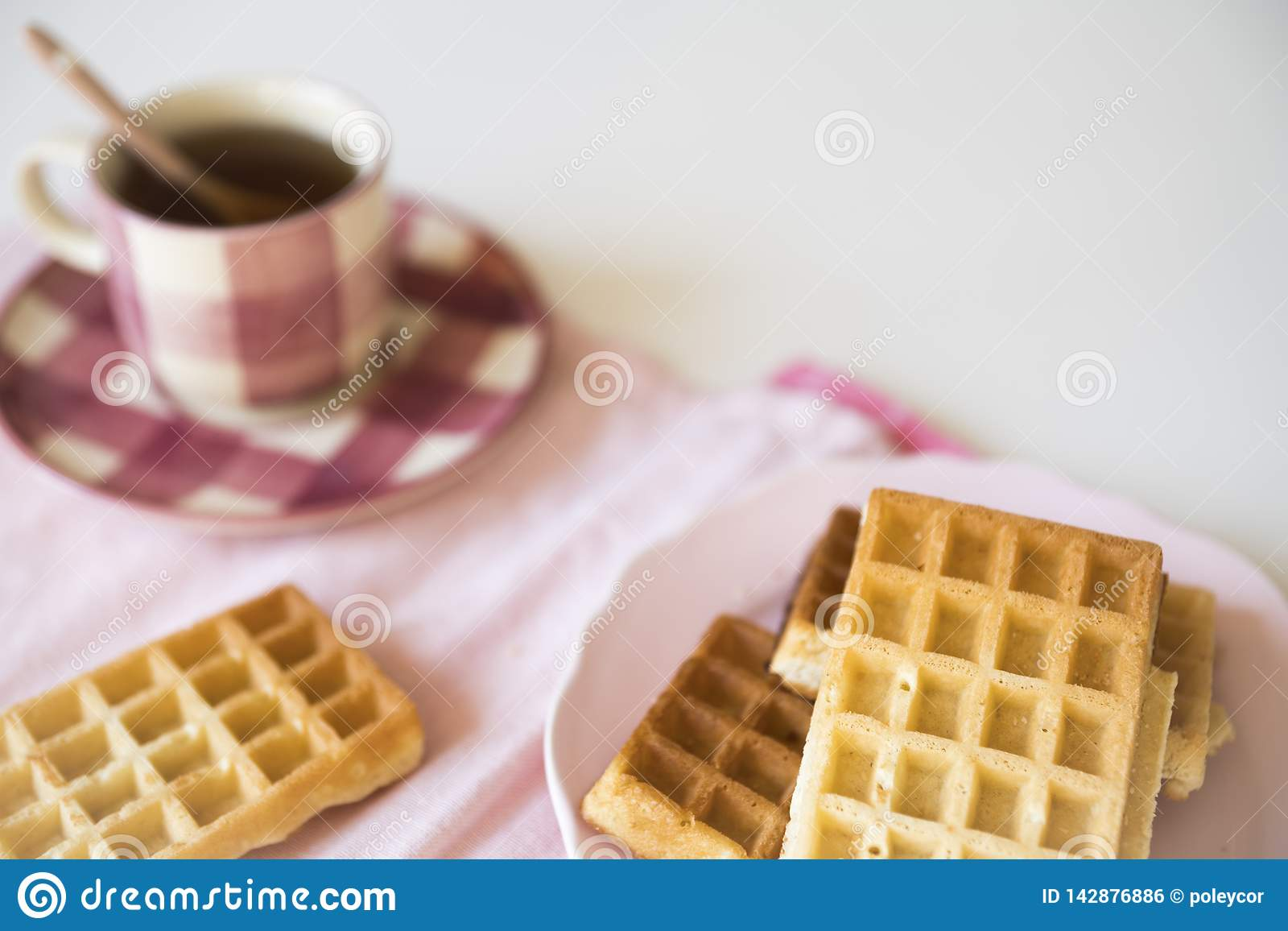Pink cup of tea and Brussel waffles on white table