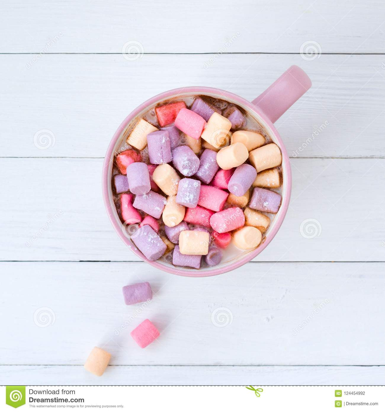 pink cup with winter cocoa with colored marshmallows on a wooden background