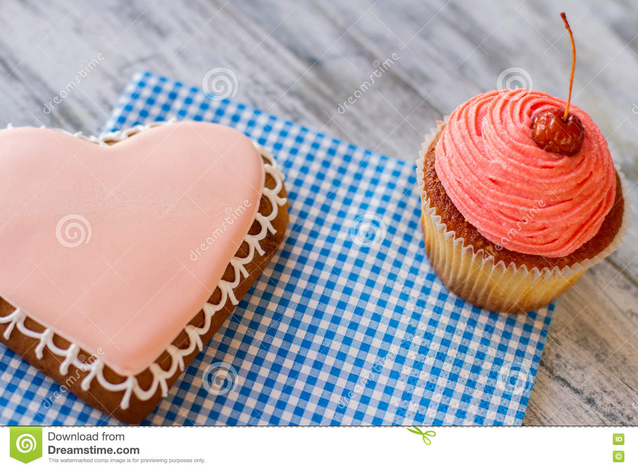 Pink cupcake and heart cookie.