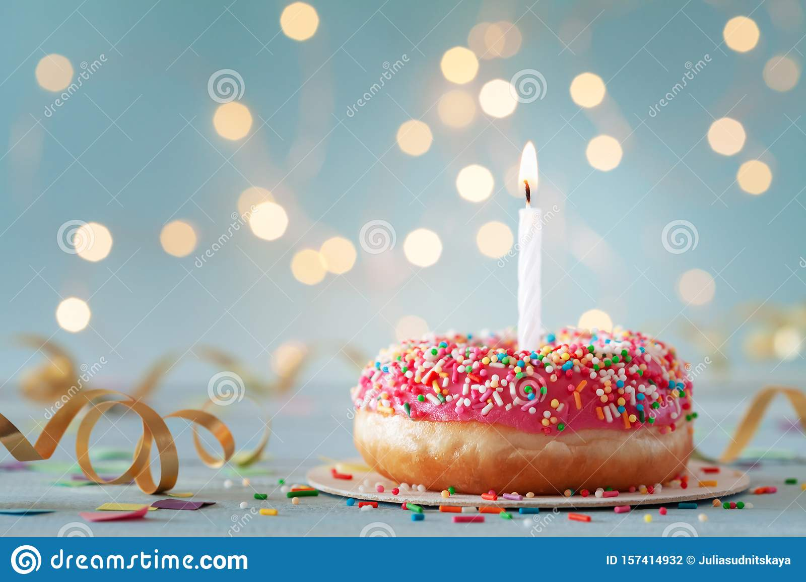 Pink donut and one burning candle against bokeh light background. Happy birthday concept
