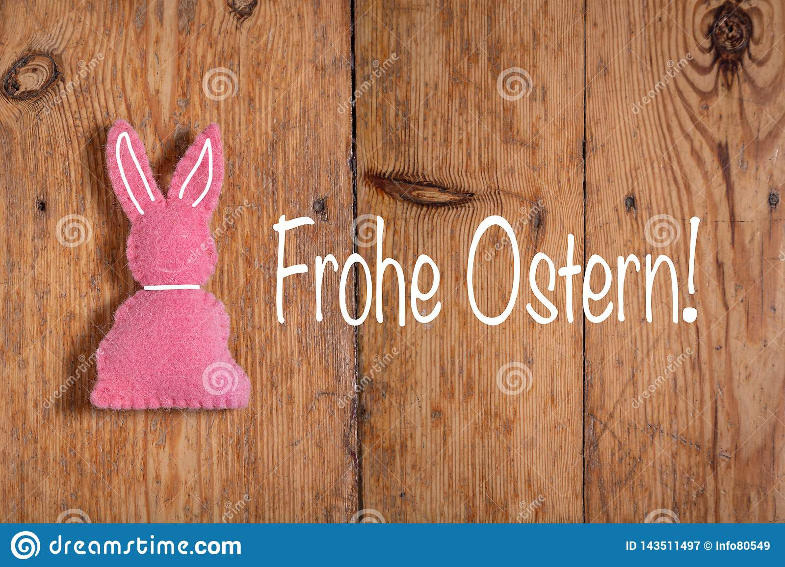Pink Easter bunny with text `Frohe Ostern` and a wooden background. Translation: `Happy Easter`