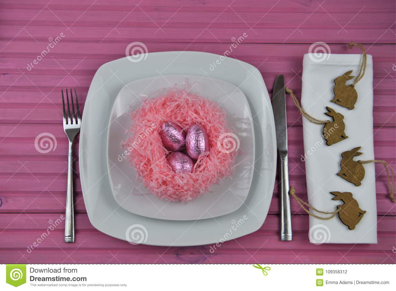 Pink Easter time table place setting in white with chocolate wrapped eggs and bunny rabbit shape decorations