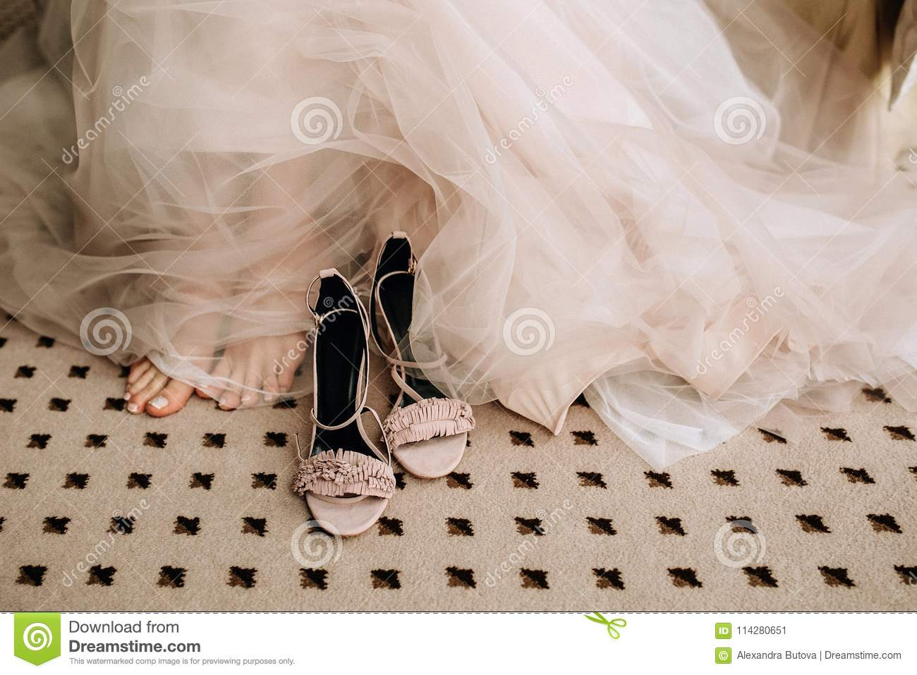 f6be7916f3dd9a Pink elegant shoes of the bride`s barefoot on the floor next to the feet  and a wedding gentle dress made of translucent fabric