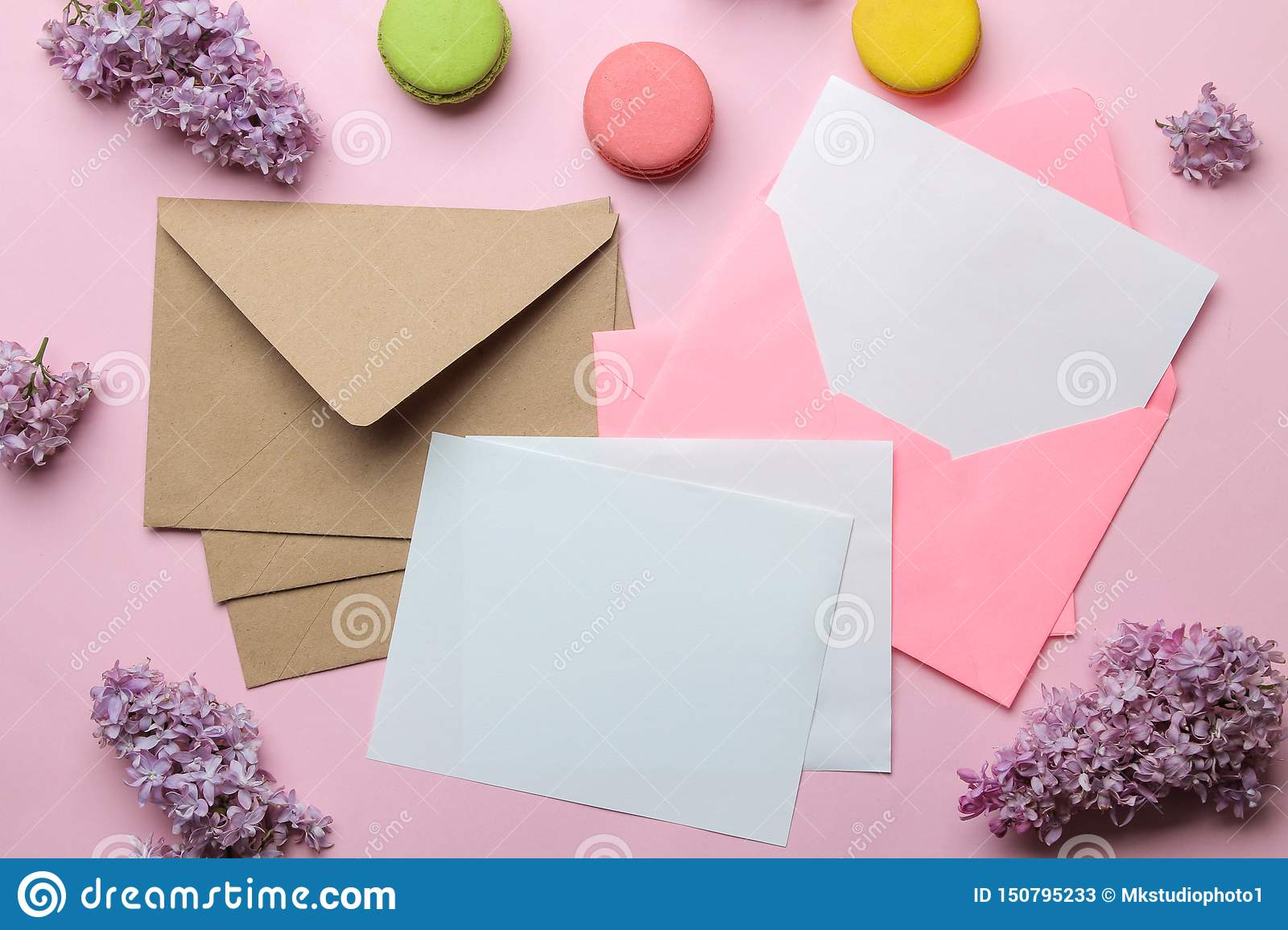 Pink envelope with a blank for text and a branch of lilac and macarons on a bright trendy pink background. top view