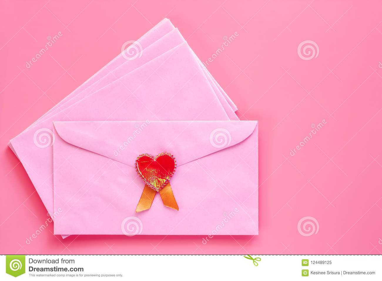 Pink envelope with red heart on pink background