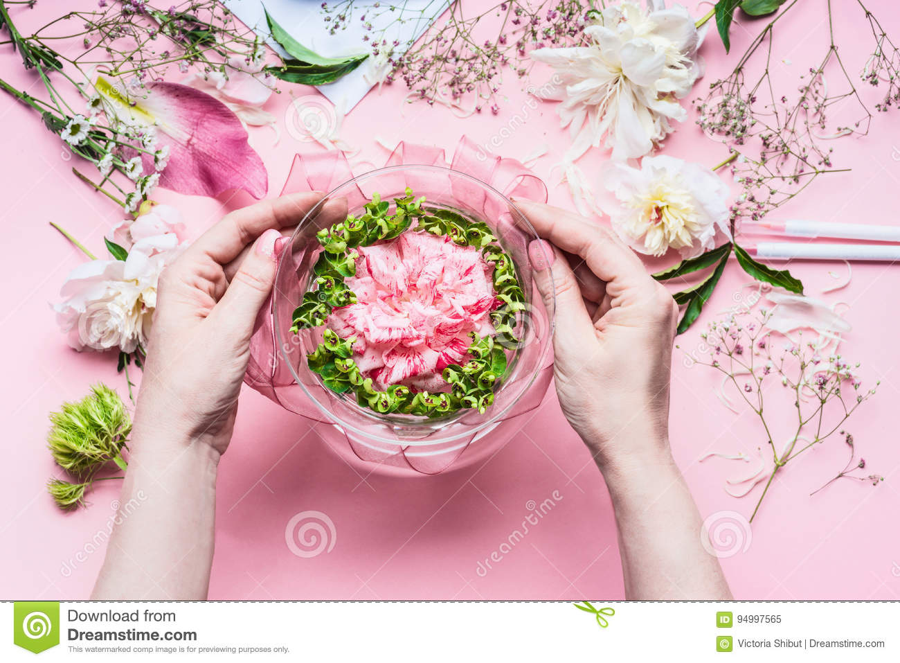 Pink Florist workspace with Lilies and other flowers, glass vase with water. Female hands making Festive Flowers arrangements