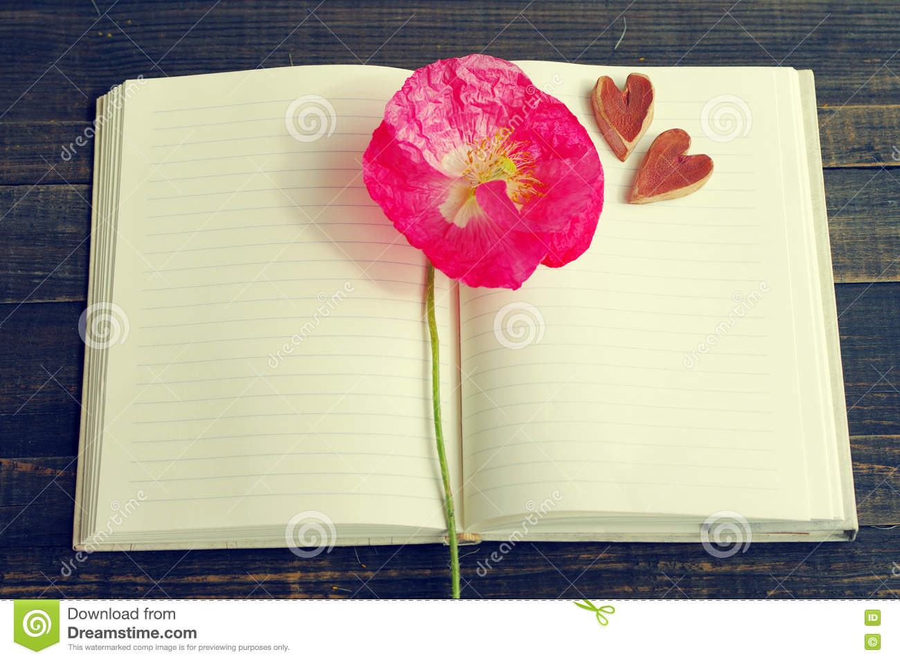 Pink Flower Of Poppy On An Open Notebook And Two Decorative Hearts