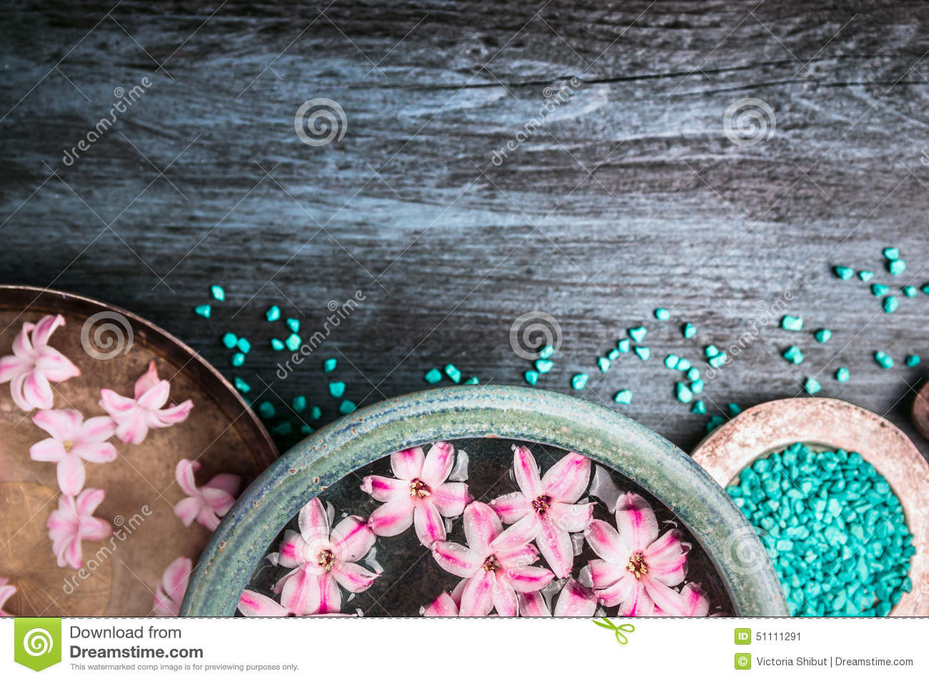 Pink flowers in bowls with water and blue sea salt on wooden table, wellness background, top view