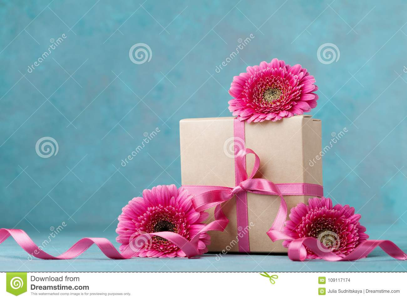 Pink Flowers And Gift Box With Ribbon On Turquoise Table Greeting