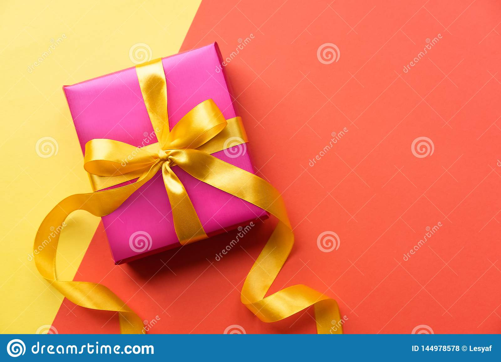 Pink gift box on color background. Yellow and orange background with present. Copy space.