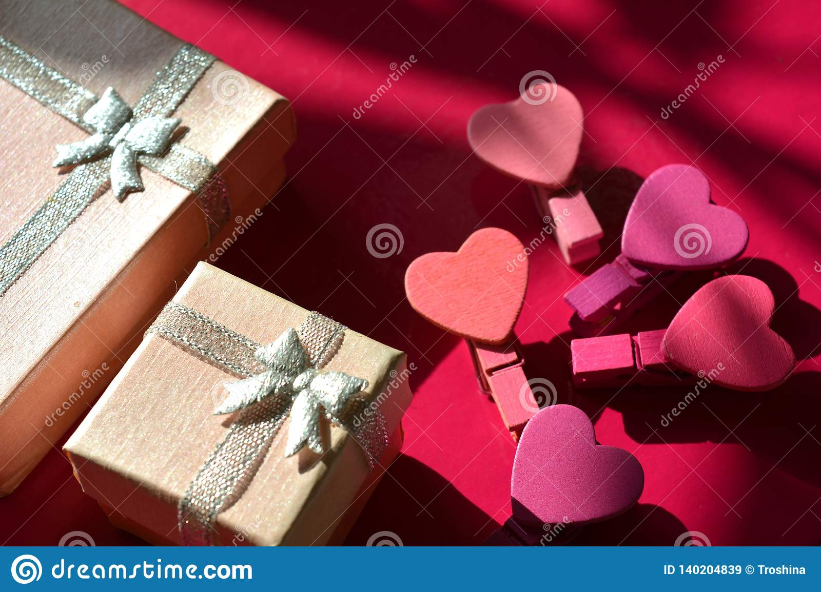 Pink gift box and decorative hearts pink background