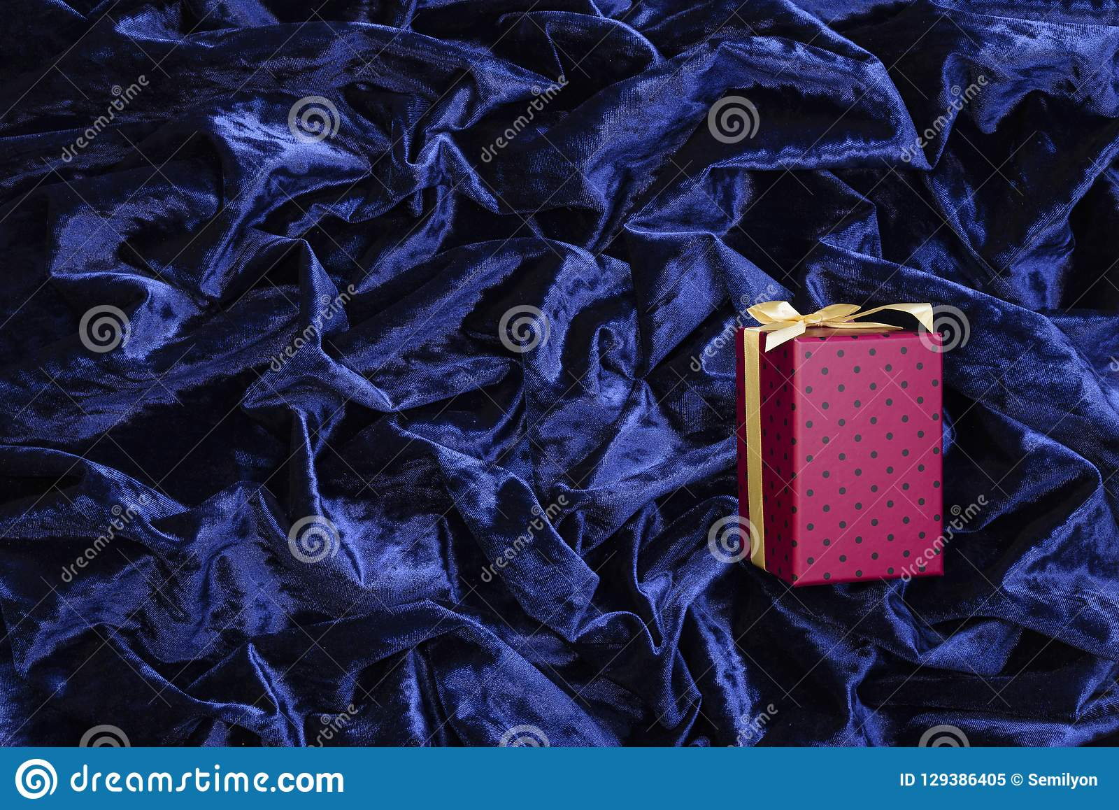 Pink gift box on a delicate blue silk surface with highlights, arranged in waves and pleats