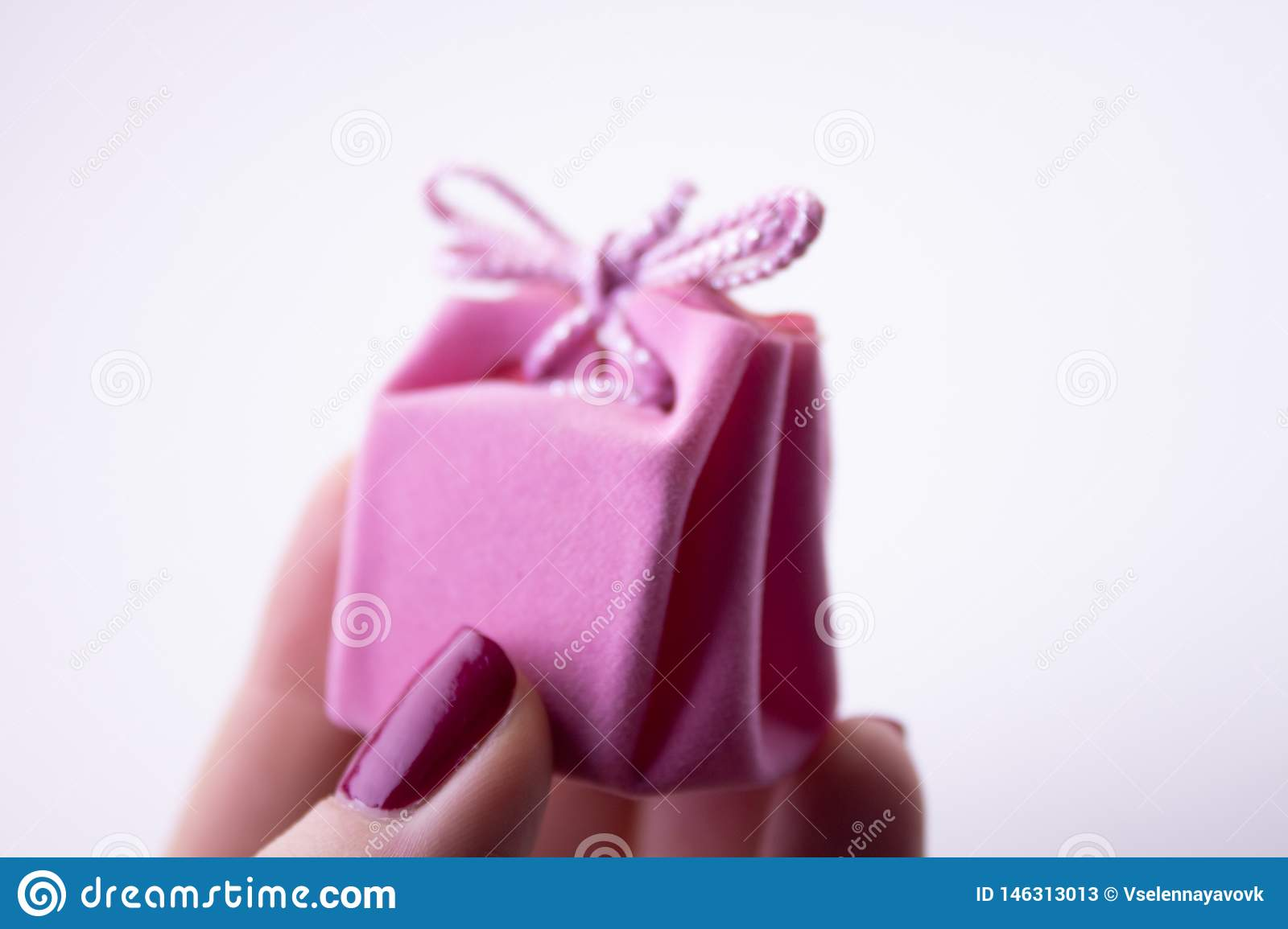 Pink gift box with ribbon for decorations in hand. Festive gift to a girl or woman