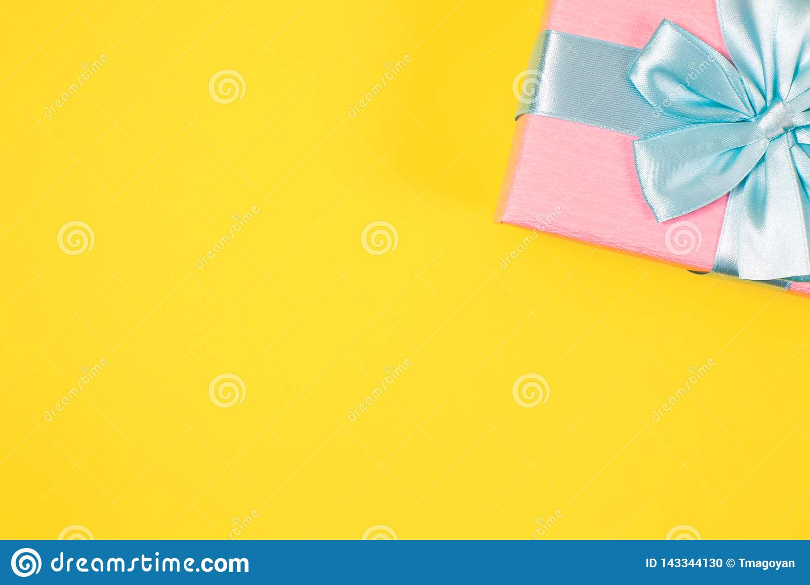 Pink gift box tied with blue ribbon with bow at the top on yellow background. Copy space for text. Minimal flat lay. Top view.
