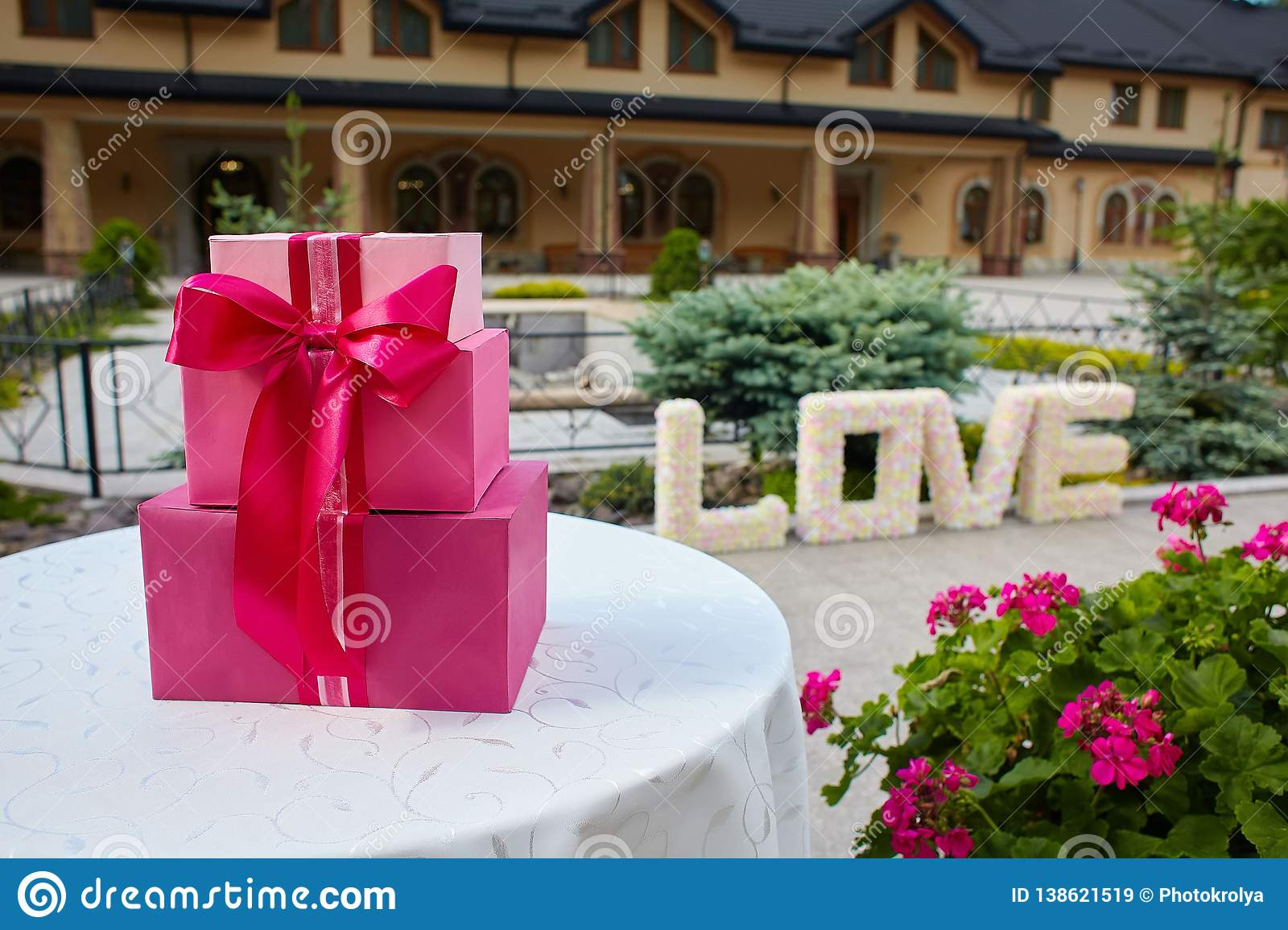 Pink gift boxes on a circle white table outdoors. Word Love made of paper flowers outdoors.