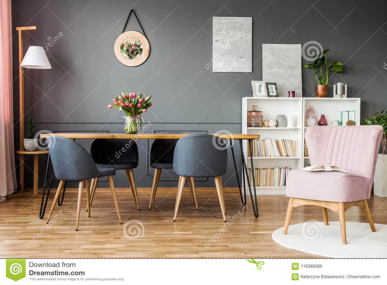 Pink Armchair Next To Grey Chairs At Wooden Table With Tulips In Elegant Dining Room Interior